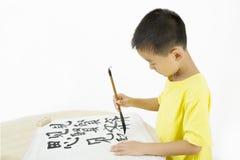 Ein Kind, das chinesische Kalligraphie schreibt Stockfoto