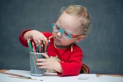 Ein Kind, das an einem Schreibtisch mit Papier und farbigen Bleistiften sitzt Lizenzfreies Stockfoto