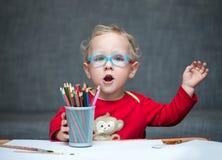 Ein Kind, das an einem Schreibtisch mit Papier und farbigen Bleistiften sitzt Lizenzfreie Stockfotografie