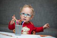 Ein Kind, das an einem Schreibtisch mit Papier und farbigen Bleistiften sitzt Lizenzfreie Stockfotos