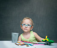 Ein Kind, das an einem Schreibtisch mit Papier und farbigen Bleistiften sitzt Stockfotos