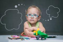 Ein Kind, das an einem Schreibtisch mit Papier und farbigen Bleistiften sitzt Lizenzfreies Stockbild