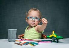 Ein Kind, das an einem Schreibtisch mit Papier und farbigen Bleistiften sitzt Lizenzfreie Stockbilder