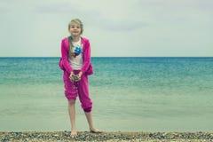 Ein Kind, das im kühlen Wetter auf der Küste spielt Lizenzfreies Stockbild