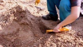 Ein Kind, das im Sand, heißer Tag des Sommers spielt stock video footage