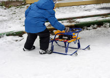 Ein Kind, das mit einem Schlitten spielt Lizenzfreies Stockbild