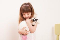 Ein Kind, das mit einem weißen Kätzchen spielt Stockbild
