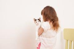 Ein Kind, das mit einem weißen Kätzchen spielt Stockfoto