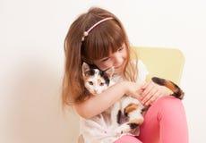 Ein Kind, das mit einem weißen Kätzchen spielt Lizenzfreie Stockfotografie