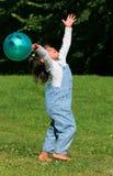 Ein Kind, das mit einer Kugel spielt Lizenzfreie Stockfotos