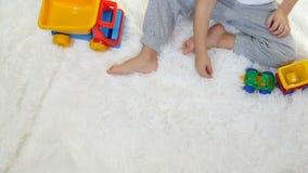 Ein Kind, das mit Spielzeuglastwagen, in der Zeitlupe, auf einem weißen Hintergrund spielt