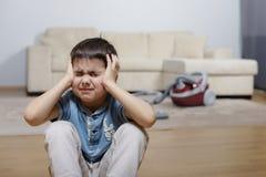 Ein Kind, das seinen Kopf und Leiden hält Lizenzfreies Stockbild