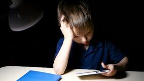 Ein Kind, das zu Hause am Tisch eine Karikatur nachts unter Verwendung eines Smartphone durchdacht aufpassend sitzt stock footage