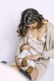Ein Kind in den Armen seiner Mutter Er versteckt sein Gesicht mit seinen Händen Stockbild