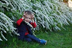 Ein Kind des kleinen Jungen ist, der Junge glücklich, der den Affen in einem Sommer spielt Stockbilder