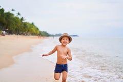 Ein Kind in einem Hut läuft und lächelt - asiatischer Junge in einem Hut, unscharfer Hintergrund lizenzfreies stockfoto