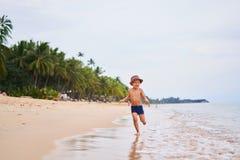 Ein Kind in einem Hut läuft und lächelt - asiatischer Junge in einem Hut, unscharfer Hintergrund lizenzfreie stockbilder