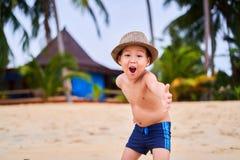 Ein Kind in einem Hut steht auf dem sandigen Strand des Ozeans stockfotografie