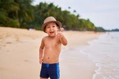 Ein Kind in einem Hut steht auf dem sandigen Strand des Ozeans stockfotos