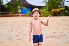 Ein Kind in einem Hut steht auf dem sandigen Strand des Ozeans stockbilder