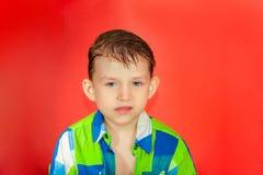 Ein Kind in einem karierten Hemd betrachtet die Kamera mit Verachtung Porträt eines stolzen und hochmütigen Jungen auf einem rote lizenzfreie stockfotos