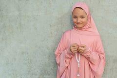 Ein Kind in einem rosa hijab mit Perlen in seinen Händen mit Kopienraum Religiöses Lebensstilkonzept der Leute lizenzfreie stockfotos