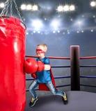 Ein Kind in einem Superheldkostüm-Athletenboxer Boxer schlägt eine boxende Tasche in der Turnhalle lizenzfreie stockfotografie