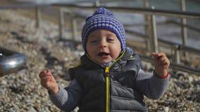 Ein Kind in einem Winterhut lächelt an der Kamera stock video