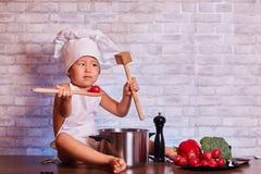 Ein Kind, ein Junge in einem Schutzblech, sitzt auf dem Küchentisch, in der Kappe eines Kochs, hält hölzerne Löffel und eine Toma stockfoto
