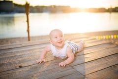 Ein Kind ein Junge, ein Jähriges, blonder Mann liegt auf seinem Magen auf hölzernem Dock, Pier in gestreifter Kleidung, Mittel na Lizenzfreie Stockfotos