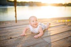 Ein Kind ein Junge, ein Jähriges, blonder Mann liegt auf seinem Magen auf hölzernem Dock, Pier in gestreifter Kleidung, Mittel na Stockfoto