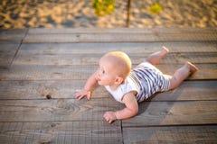 Ein Kind ein Junge, ein Jähriges, blonder Mann liegt auf seinem Magen auf hölzernem Dock, Pier in gestreifter Kleidung, Mittel na Lizenzfreie Stockbilder