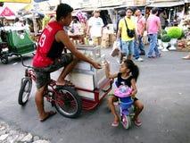 Ein Kind kauft Süßigkeit von einem Straßenhändler Lizenzfreie Stockfotografie