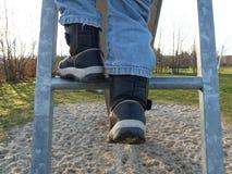 Ein Kind klettert oben eine Leiter Lizenzfreie Stockfotos