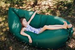 Ein Kind legt auf einem Stillstehen auf einem Luftsofa im Wald Lamzac Reise, Familienurlaub im Wald im Sommer stockfotografie