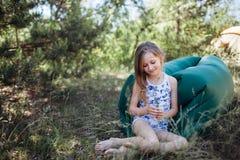 Ein Kind legt auf einem Stillstehen auf einem Luftsofa im Wald Lamzac Reise, Familienurlaub im Wald im Sommer lizenzfreie stockfotografie