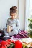 Ein Kind liest ein Buch auf dem Fensterbrett Das Konzept von Weihnachten Lizenzfreie Stockbilder