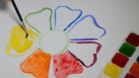 Ein Kind malt eine Blume Mit Bürste und Farben stock footage