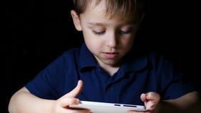 Ein Kind mit einer Karikatur eine Karikatur nachts unter Verwendung eines Smartphone zu Hause aufpassend und lächelnd, Nahaufnahm stock footage