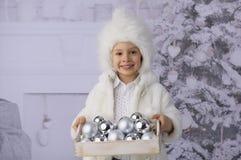 Ein Kind mit Weihnachtsgeschenken und Weihnachtsbaum stockbild