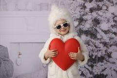 Ein Kind mit Weihnachtsgeschenken und Weihnachtsbaum lizenzfreie stockbilder