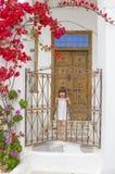 Ein Kind nahe einer alten Tür mit Treppen und Blumen Stockfoto