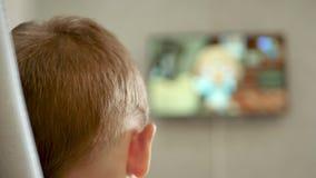 Ein Kind passt eine Karikatur auf, auf einem Stuhl zu sitzen Der Fernsehschirm ist- unscharf stock video footage