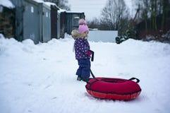 Ein Kind reitet einen Käsekuchen mit einem schneebedeckten Hügel lizenzfreie stockbilder
