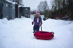 Ein Kind reitet einen Käsekuchen mit einem schneebedeckten Hügel stockfotografie