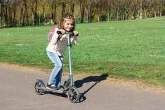 Ein Kind reitet einen Roller Stockfotos