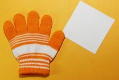 Ein Kind-` s orange Handschuh mit weißen Streifen liegt auf der gelben Oberfläche Stockbilder