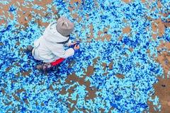 Ein Kind sammelt Konfettis nach dem Feiertag Blaue Konfettis zerstreut aus den Grund nach einem Karneval oder einem Geburtstag fe lizenzfreie stockbilder