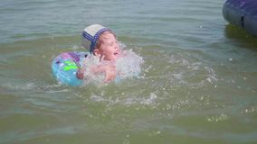 Ein Kind schwimmt auf einem aufblasbaren Kreis im Meer Glückliche Kindheit Positive Gefühle stock video
