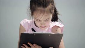 Ein Kind sitzt auf einem Stein nahe dem adriatischen Meer und zeichnet ein Bild stock video footage